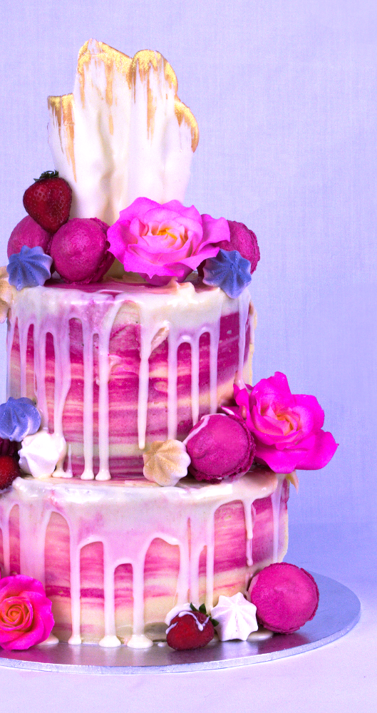 Pink two-tiered cake with an array of flowers and icing dripping over the sides