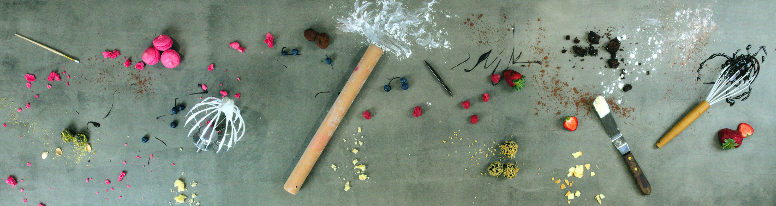 A long concrete bench-top with an assortment of cake ingredients and utensils